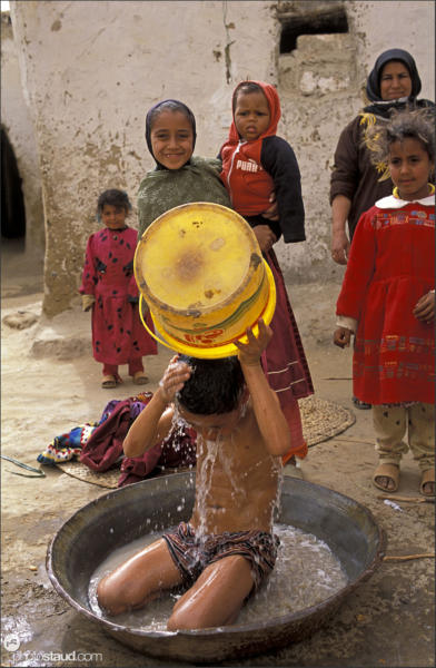 Bedouin children having outdoor bath, El Ris village, Libyan Desert, Egypt
