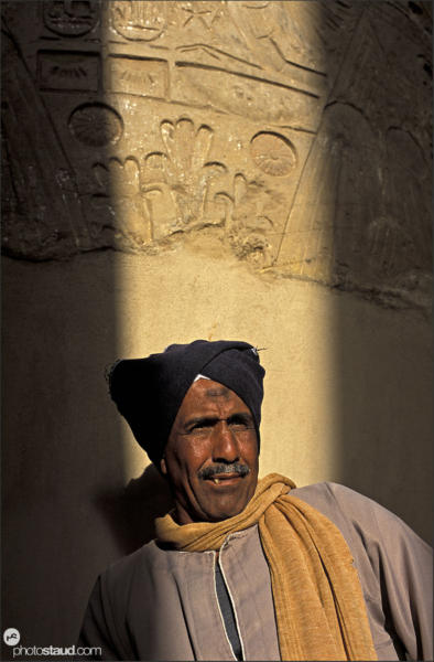 Egyptian man leaning against massive column in The Great Hypostyle Hall at the Temple of Amun, Karnak, Luxor - Thebes, Egypt