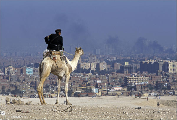 Policeman on a camel watching smoking Cairo, Egypt