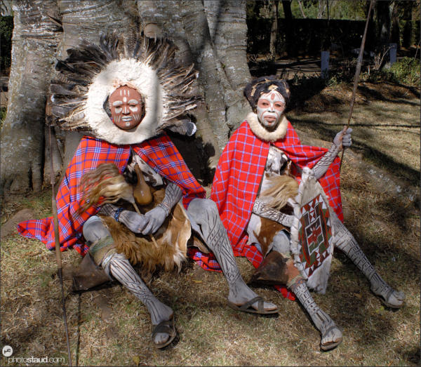 Kikuyu dancers wearing traditional costumes sitting under tree, Kenya