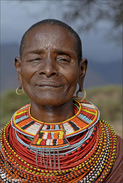 Old Samburu woman wearing colorful tribal ornaments of bead necklaces, Kenya