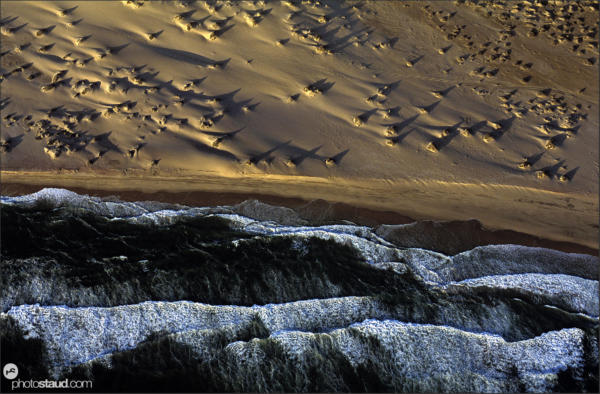Waves of the Atlantic Ocean meeting sand of the Namib Desert Aerial photograph, Namibia