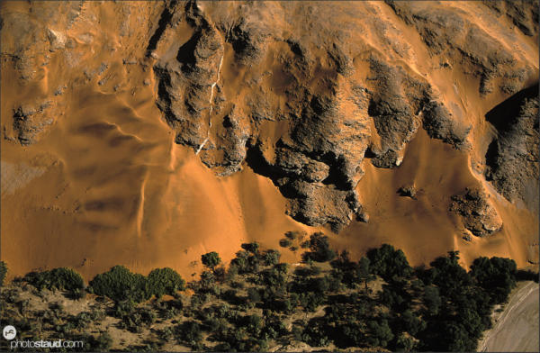 Sand, rock and vegetation blending in the Namib Desert Aerial photograph