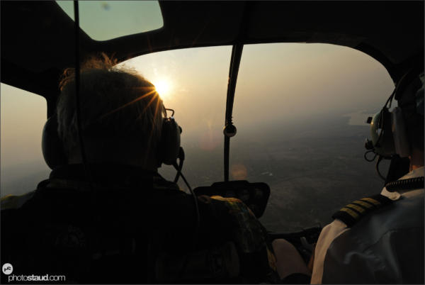 Pilots in a helicopter flying against setting sun, Zambia