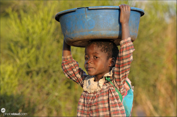 Zambian child carrying laundry on head, Zambia