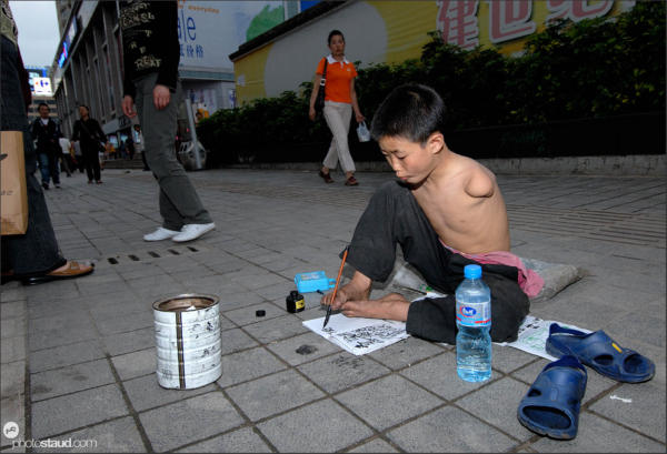 Armless Chinese boy writing with his feet, Kunming, Yunnan, China