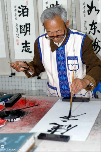 Calligraphy master uses both hands for his artwork, Yunnan, China