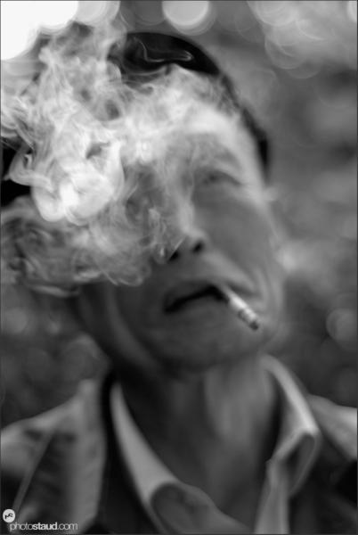 Elderly Chinese man smoking, China