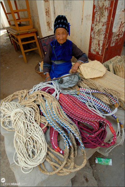 Old Chinese woman selling ropes at market in Wase, Yunnan, China