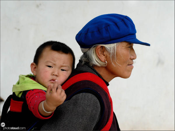 Naxi woman carrying baby, Lijiang, Yunnan, China