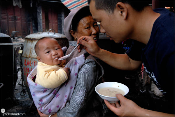Chinese father feeding his son, Lijiang, Yunnan, China