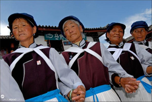Old Naxi women dancing hand-in-hand on the Lijiang square, Yunnan, China