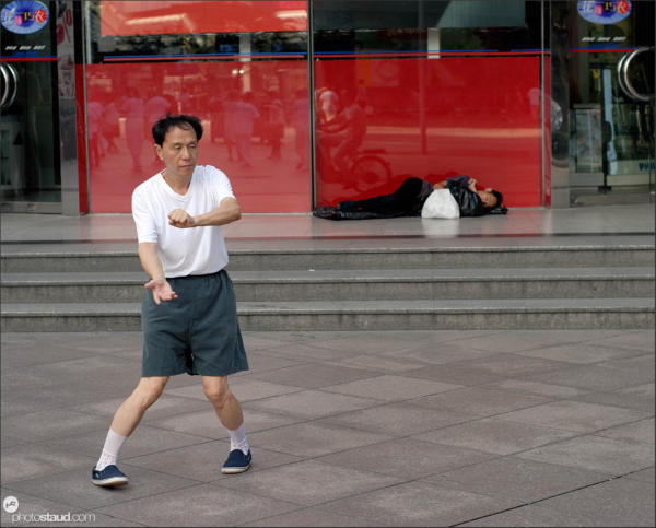 Chinese man practicing tai-chi on the Nanjing-lu road, Shanghai, China