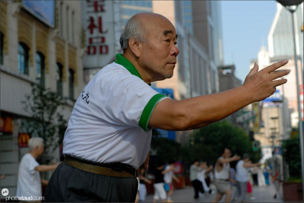 Chinese people practicing tai-chi on the Nanjing-lu road, Shanghai, China