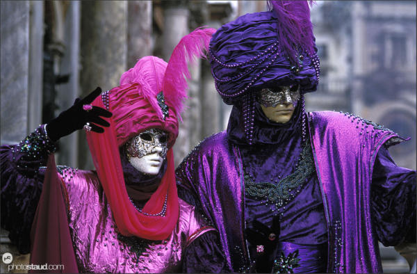 People in extravagant costumes posing Venice carnival, Italy